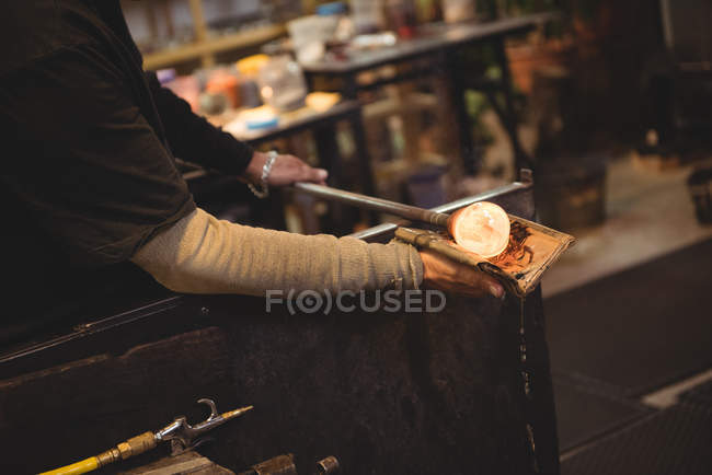 Glassblower shaping blown glass piece with wet cloth at glassblowing factory — Stock Photo