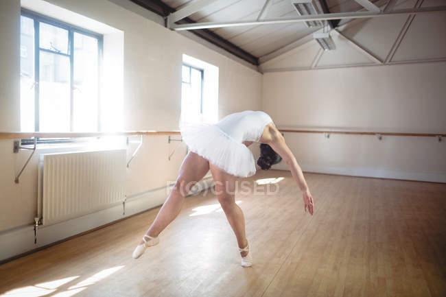 Ballerina practicing ballet and bending backwards in studio — Stock Photo