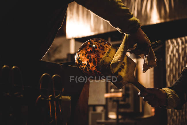 Team of glassblowers shaping molten glass at glassblowing factory — Stock Photo