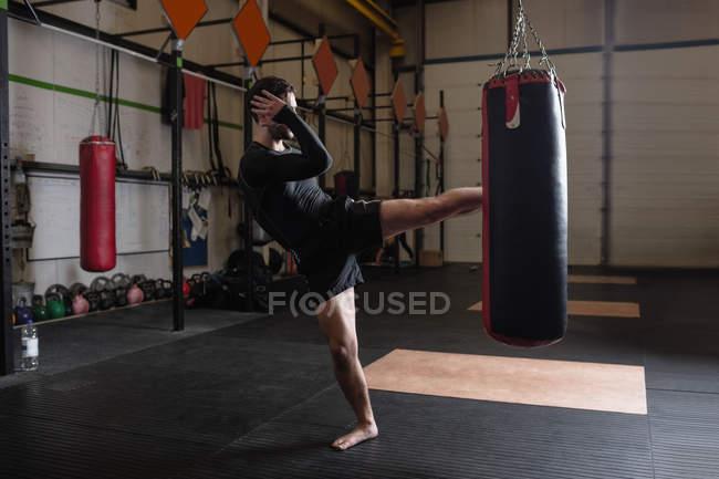 Боксер, занимающийся боксом с боксерской грушей в фитнес-студии — стоковое фото