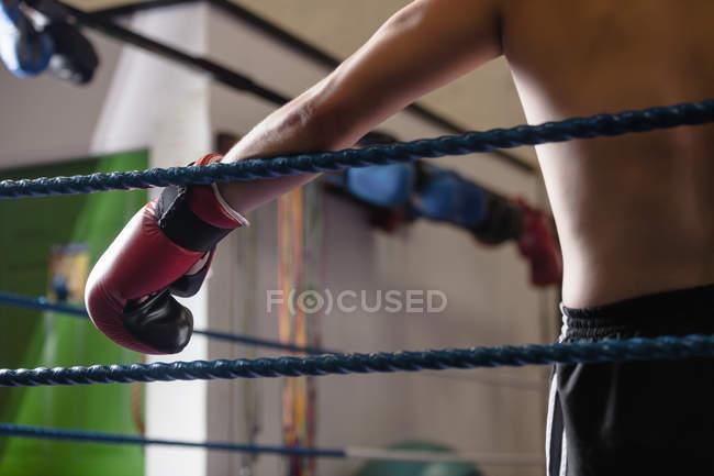 Abgeschnittenes Bild eines Boxers, der sich an Seile des Boxrings lehnt — Stockfoto