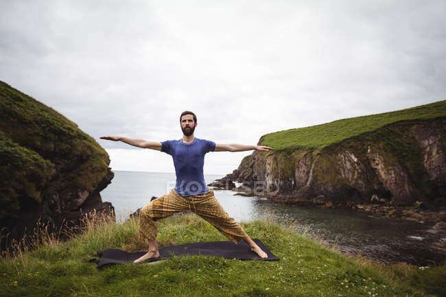 Mann führt Dehnübungen an Klippe durch — Stockfoto