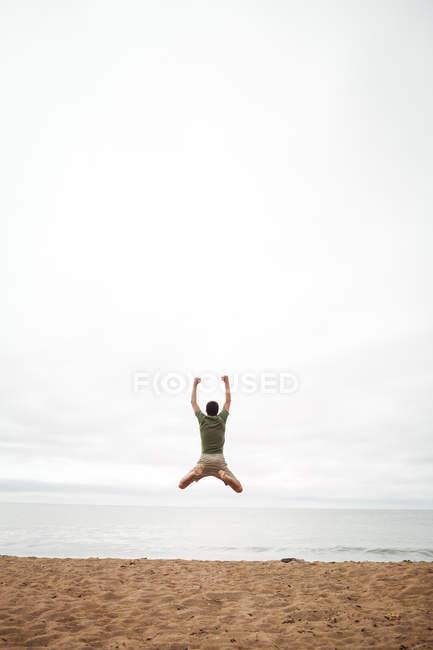 Вид сзади на человека, прыгающего на пляже — стоковое фото