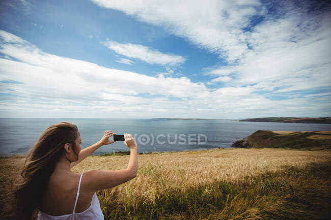 Smiling woman taking selfie with smartphone in field — Stock Photo