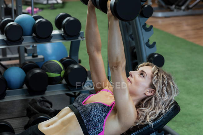 Beautiful woman lifting dumbbells at gym — Stock Photo