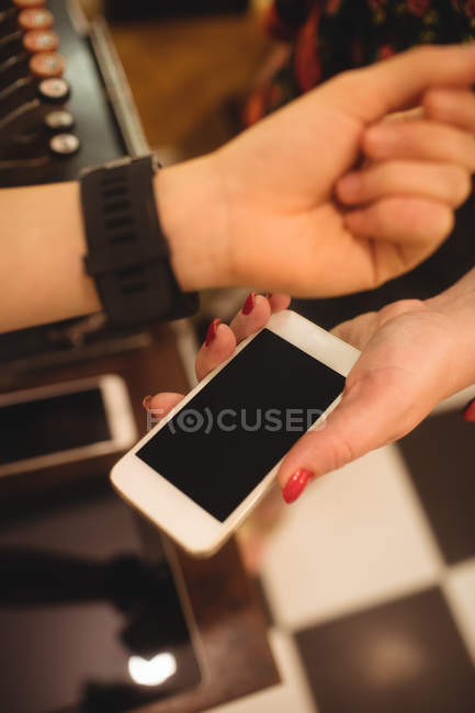 Close-up of female hands making payment through smartwatch — Stock Photo