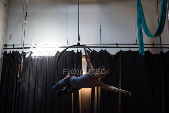 Young woman performing gymnastics on hoop in fitness studio — Stock Photo
