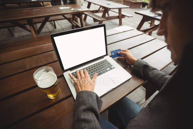 Man doing online shopping with credit card on laptop in bar — Stock Photo