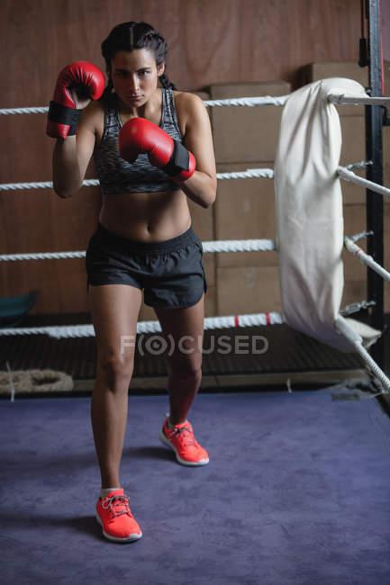 Porträt einer Boxerin in roten Boxhandschuhen im Fitnessstudio — Stockfoto