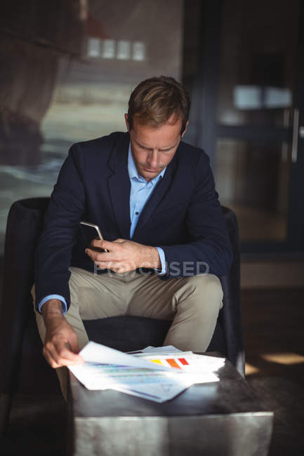 Businessman with mobile phone checking financial reports in the office — Stock Photo