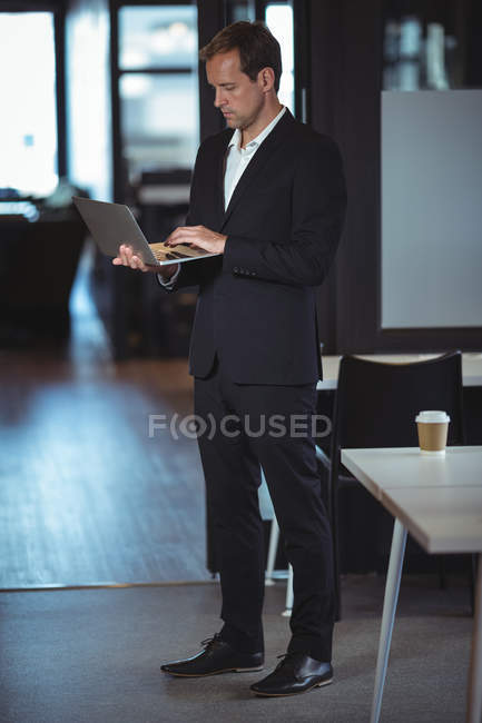 Businessman standing with a laptop in office — Stock Photo