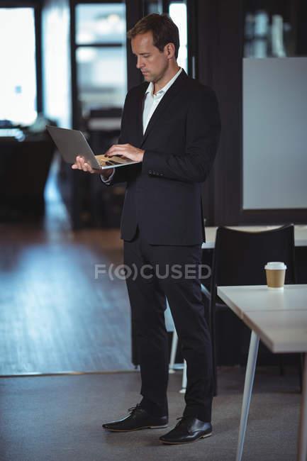 Бізнесмен, стоячи з ноутбуком в офісі — стокове фото