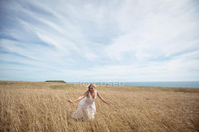 Беззаботная блондинка трогает посевы в поле — стоковое фото
