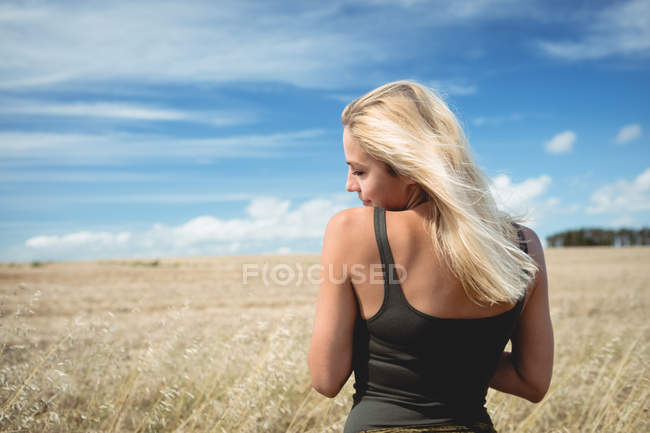 Rear view of carefree blonde woman standing in field — Stock Photo