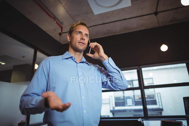 Деловой человек разговаривает по мобильному телефону в офисе — стоковое фото