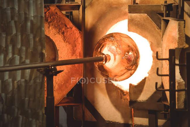 Gros plan du morceau de verre chauffé dans le four de l'usine de soufflage du verre — Photo de stock