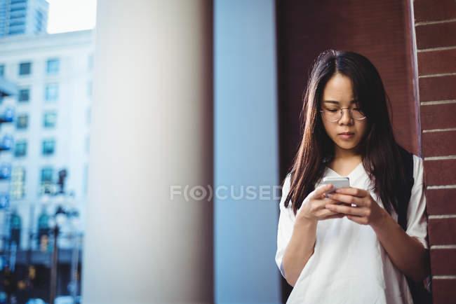 Jeune femme utilisant le téléphone portable dans le passage — Photo de stock