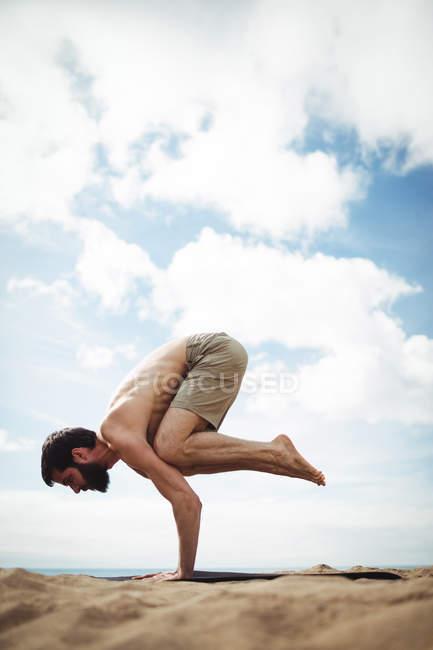 Человек, занимающийся йогой на пляже — стоковое фото