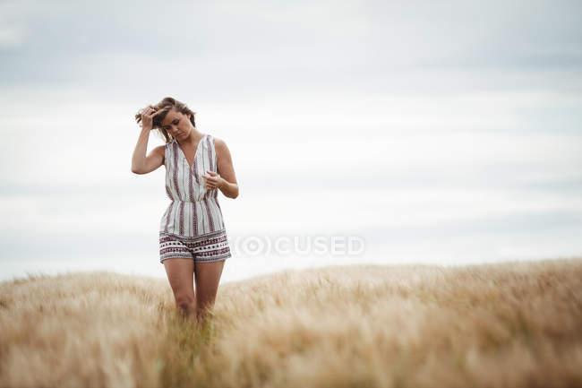 Жінка з руки в волосся, проходячи через пшенична сфера на сонячний день — стокове фото