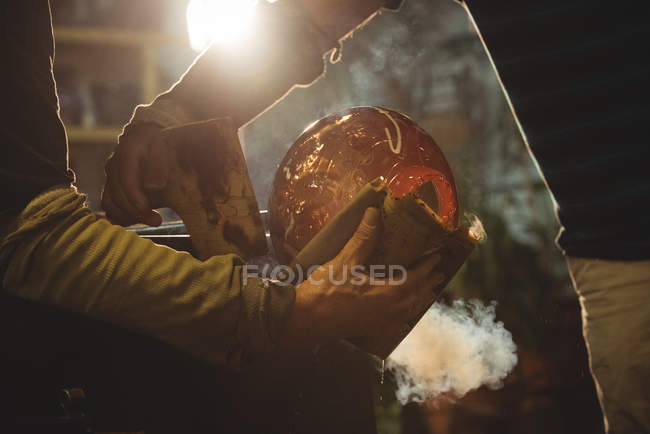 Cropped image of glassblowers shaping blown glass piece with wet cloth at glassblowing factory — Stock Photo