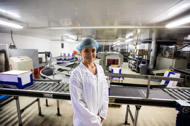 Портрет женский персонал стоя возле конвейера на заводе яйцо — стоковое фото