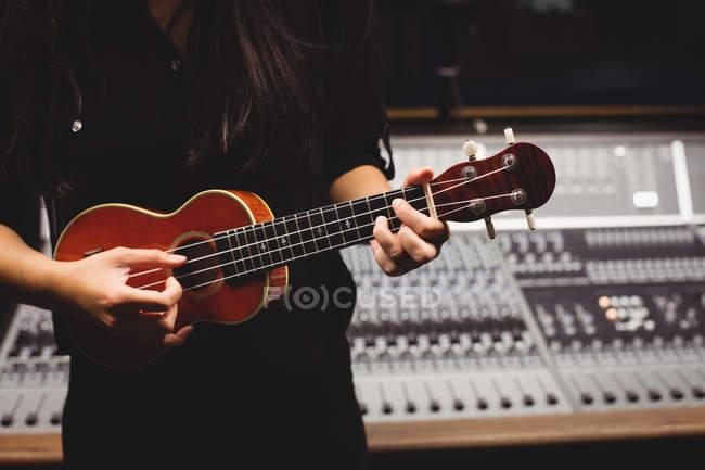 Mittelstudentin spielt Gitarre im Studio — Stockfoto