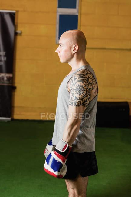 Seitenansicht eines Boxers, der mit Boxhandschuhen im Fitnessstudio steht — Stockfoto