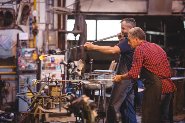 Glassblowers shaping a glass on the blowpipe at glassblowing factory — Stock Photo