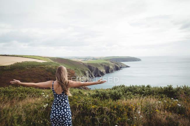 Hintere Ansicht Frau mit ausgestreckten Armen auf Klippe über Meer — Stockfoto