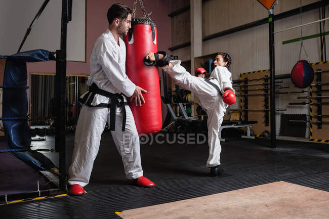 Sportswoman and sportsman practicing karate with punching bag in studio — Stock Photo