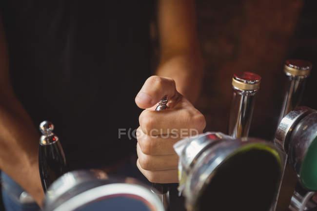 Close-up of bar tender filling beer from bar pump at bar counter — Stock Photo