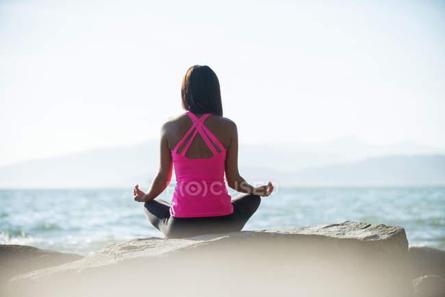 Вид сзади женщины, практикующей йогу на камне в солнечный день — стоковое фото