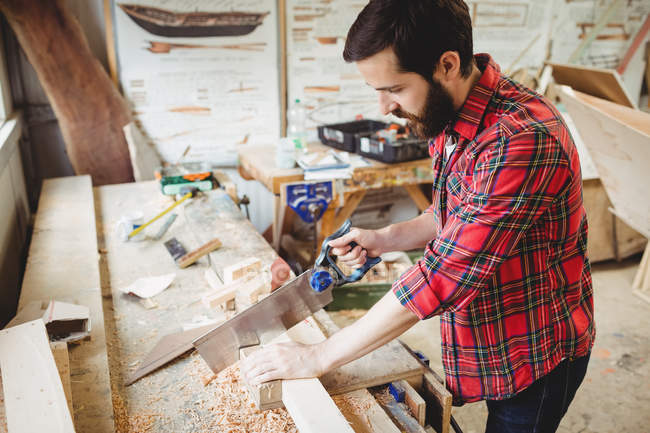 Man cutting a wooden plank at boatyard — Stock Photo