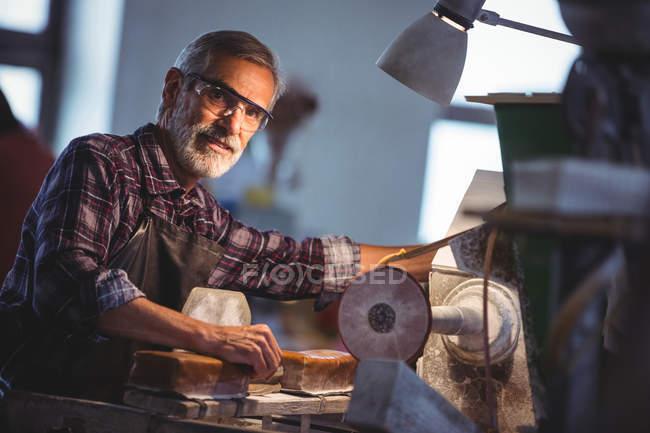Porträt eines Glasbläsers, der in der Glasbläserei an einem Glas arbeitet — Stockfoto