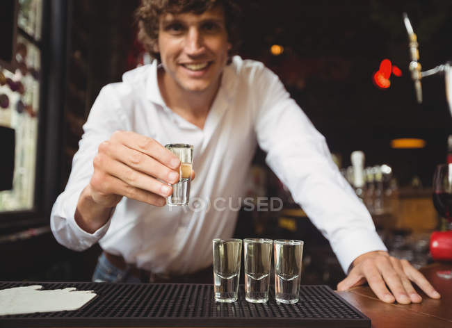 Portrait of bartender holding tequila shot glass at bar counter in bar — Stock Photo