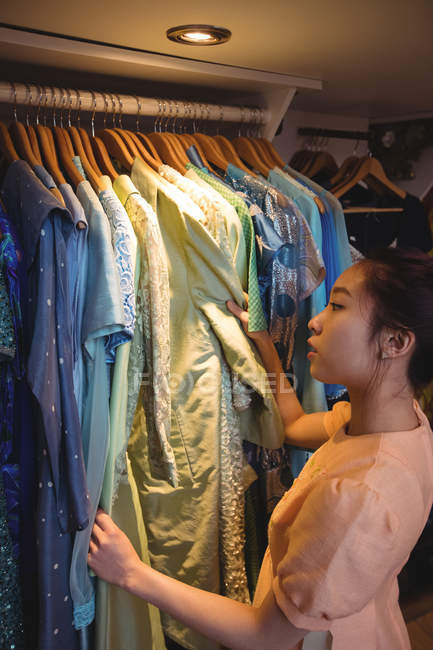 Woman selecting a clothes from hangers at boutique store — Stock Photo