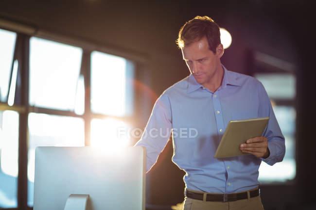 Бізнесмен, використовуючи настільного ПК і цифровий планшетний в офісі — стокове фото