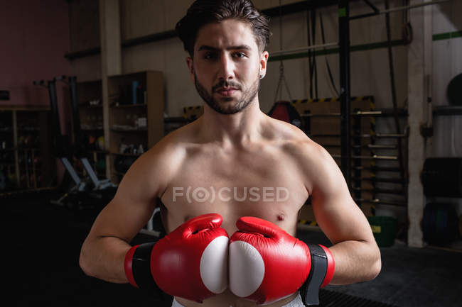 Portrait of shirtless boxer in boxing gloves looking at camera at fitness studio — Stock Photo