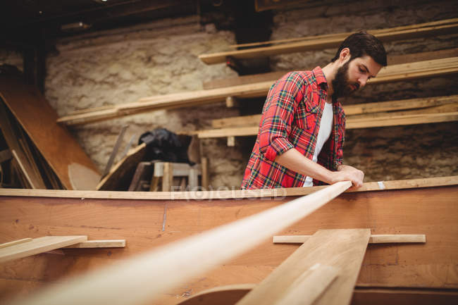 Чоловік готує дерев'яних човнах кадр на верфі — стокове фото