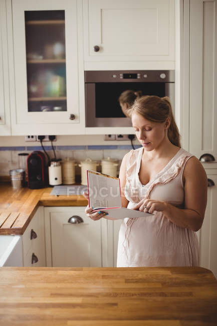 Pregnant woman reading book in kitchen at home — Stock Photo