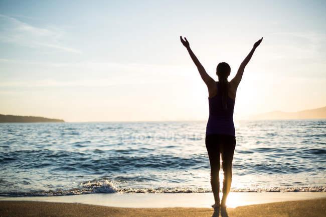 Вид сзади женщины, занимающейся йогой на пляже в солнечный день — стоковое фото
