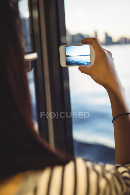 Rear view of woman taking picture of cityscape on mobile phone — Stock Photo