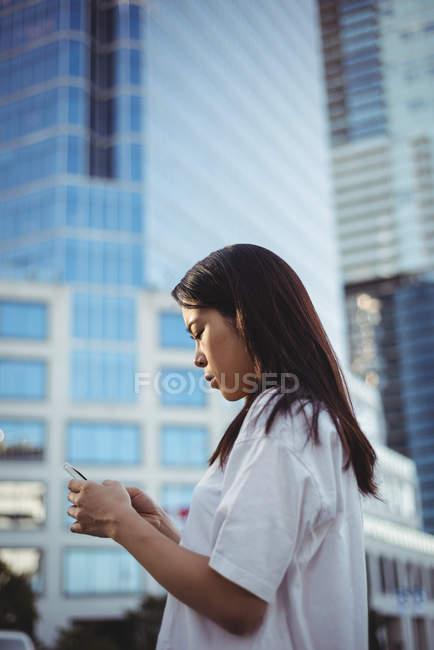 Testo di giovane donna di messaggistica sul cellulare a street — Foto stock