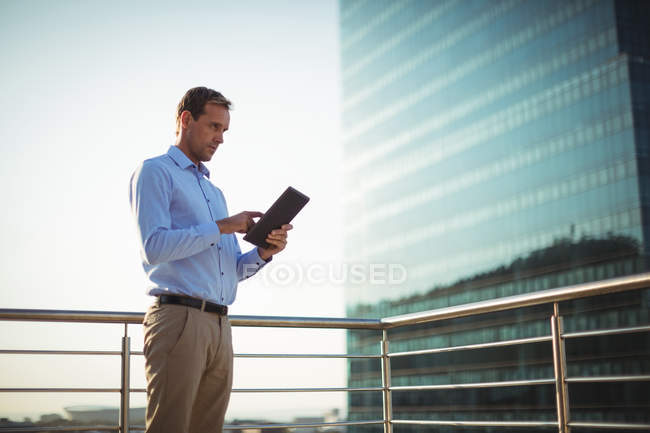 Businessman using digital tablet while standing in balcony at office — Stock Photo