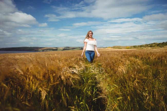 Женщина идет по пшеничному полю в солнечный день — стоковое фото