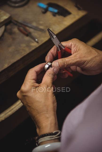 Hands of craftswoman holding pliers in workshop — Stock Photo