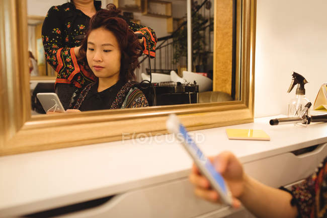 Женщина с помощью мобильного телефона при получении волос, поправил в салоне волосы — стоковое фото