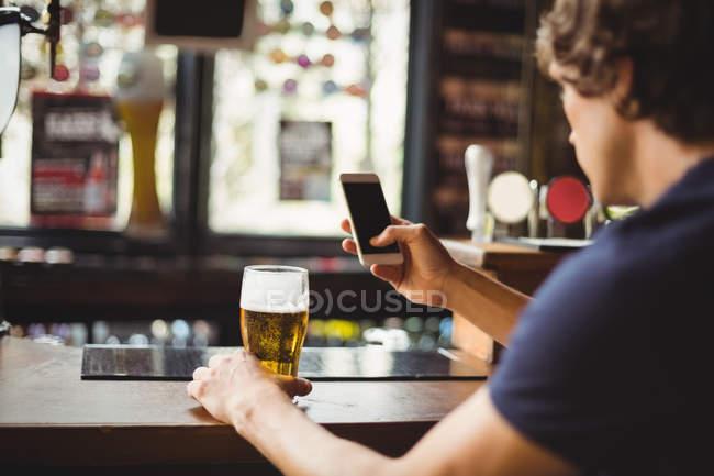 Человек, использующий мобильный телефон со стаканом пива в руке в баре — стоковое фото