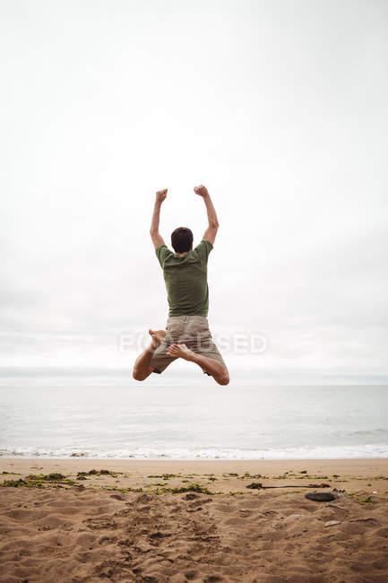 Vista posteriore dell'uomo che salta sulla spiaggia — Foto stock