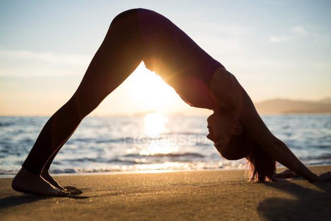 Вид сбоку на женщину, занимающуюся йогой на пляже во время заката — стоковое фото